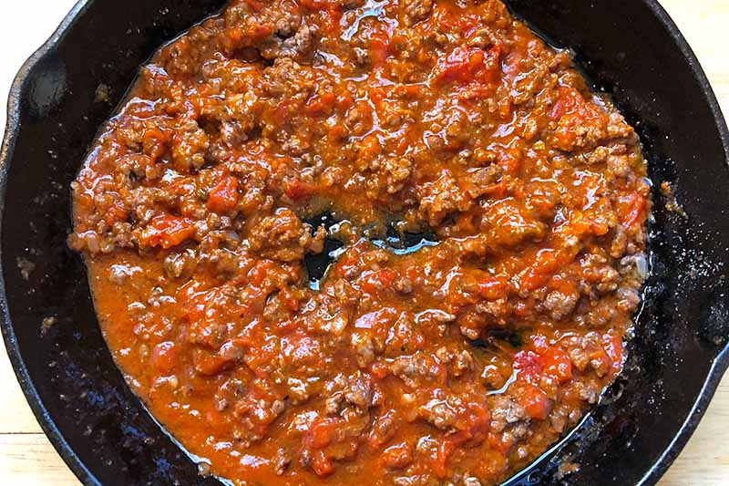 Horizontal image of cooked ground meat and tomato sauce in a skillet.