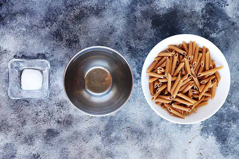 Horizontal image of a bowl of salt, a bowl of water, and a bowl of dried penne.