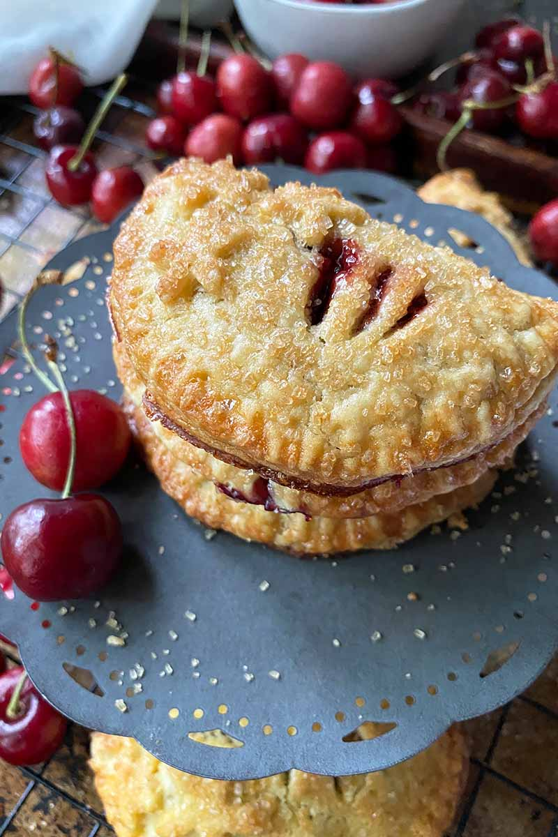 Vertical image of a stack of half-moon fruit-frilled pies on a dark cake stand next to whole cherries.