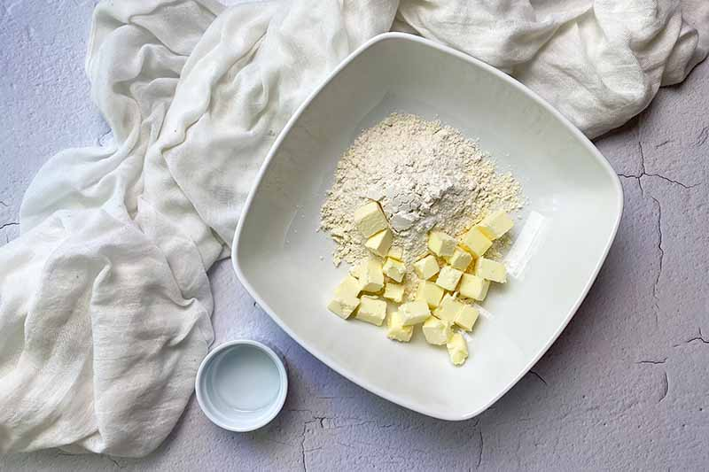 Horizontal image of cubed butter and flour in a large white bowl next to a small white dish filled with water.