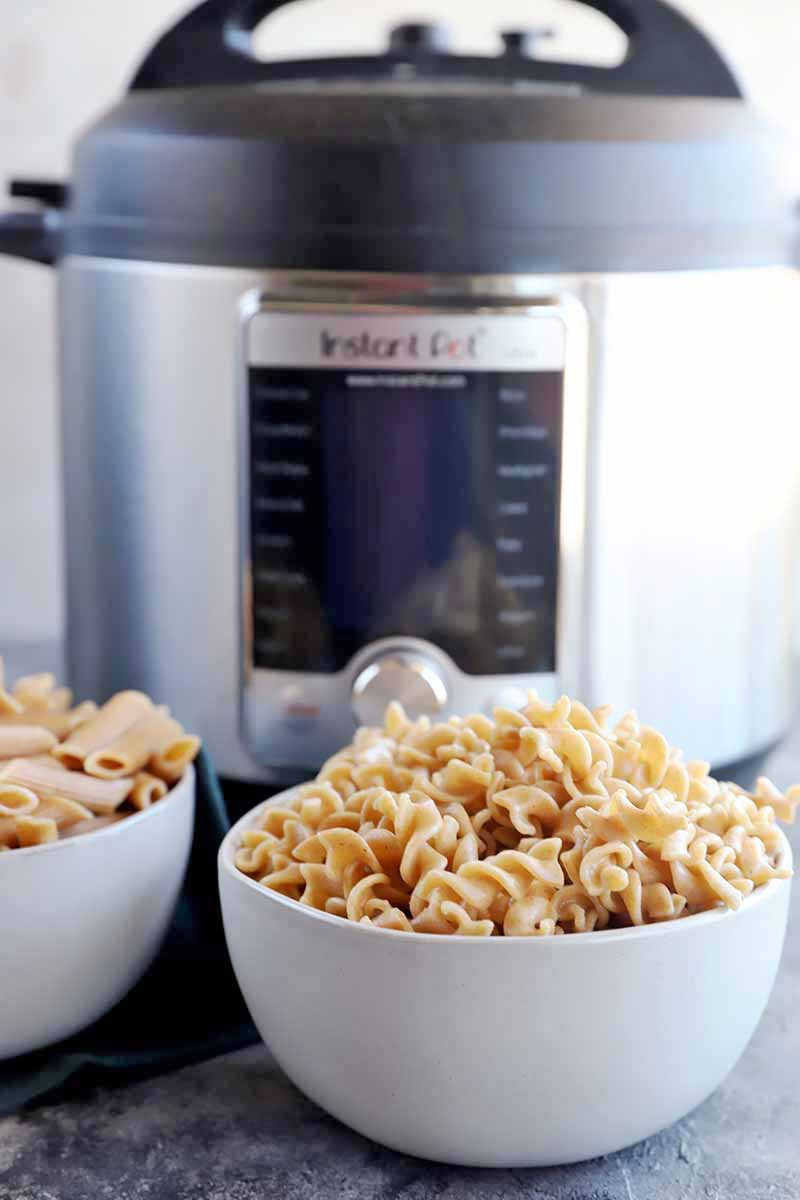 Vertical image of two small white bowls filled with plain penne and corkscrews in front of a kitchen appliance.