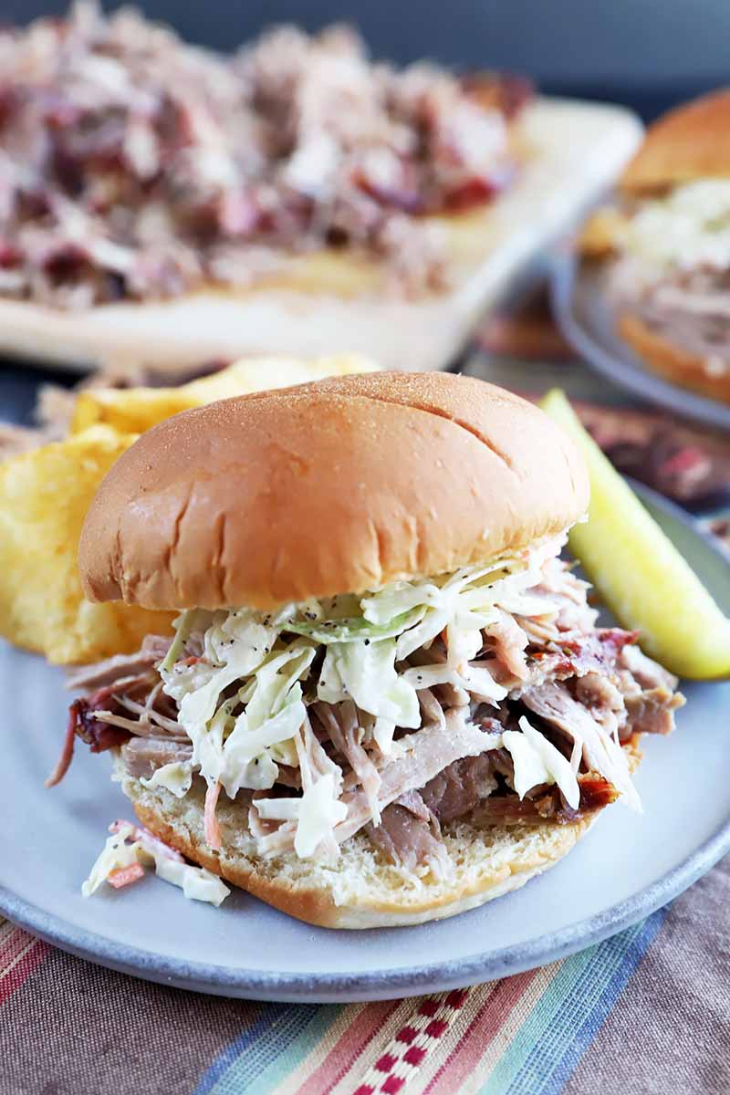 Vertical image of a sandwich filled with shredded beef and coleslaw