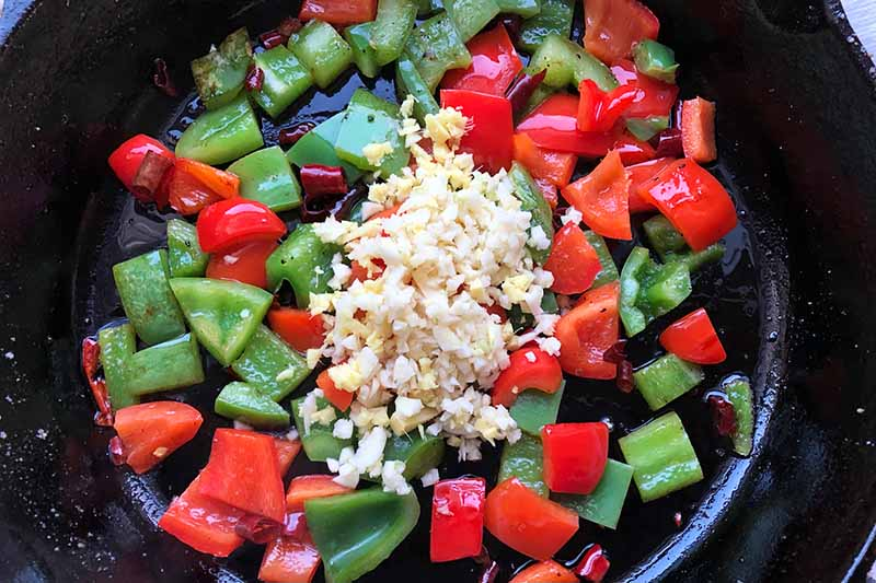 Horizontal image of cooking bell pepper pieces with garlic and ginger.