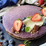 Horizontal image of a purple round dessert garnished with assorted fruit and whipped cream.