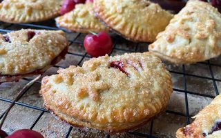 Horizontal image of assorted mini half-moon pastries filled with a red filling on a cooling rack.