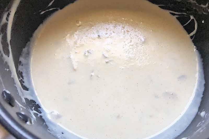 Horizontal image of a creamy seasoned white sauce in a pan.