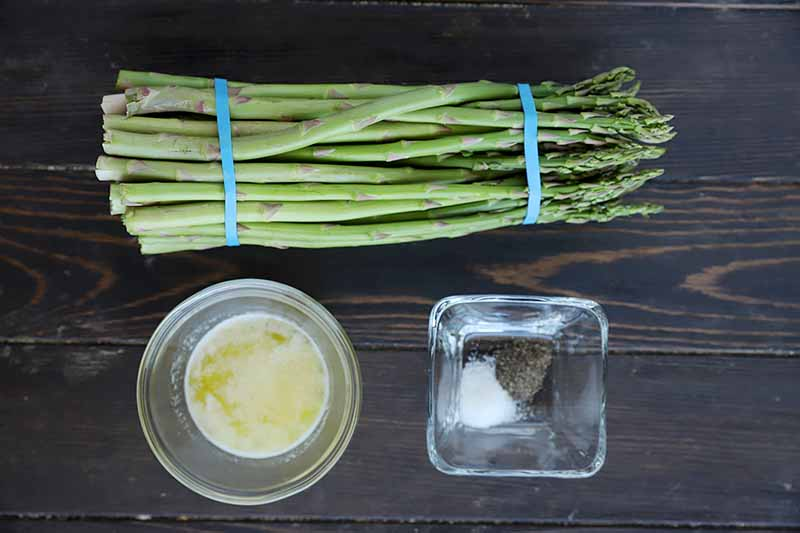 Horizontal image of a bunch of asparagus held by rubber bands, a dish of melted butter, and a dish of seasonings.