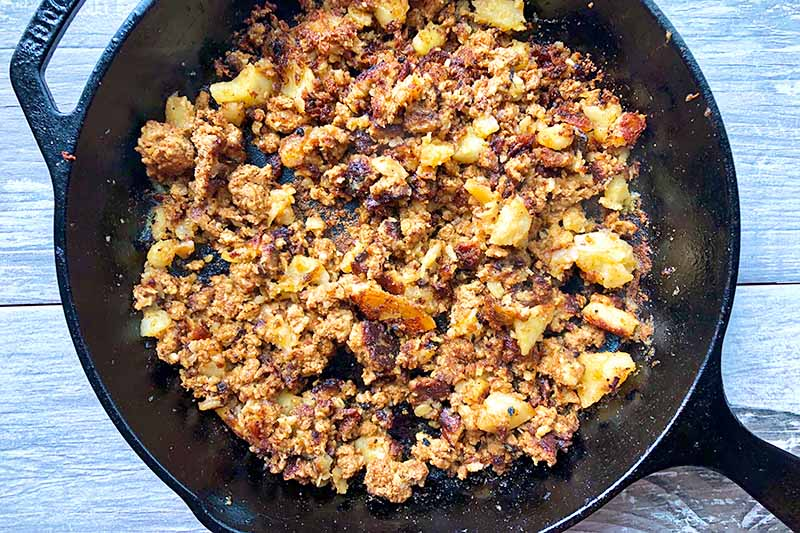 Horizontal image of cooking a mixture of vegetable and spiced ground meat in a pan.