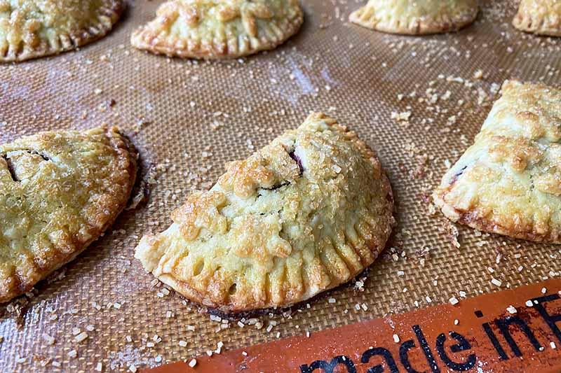 Horizontal image of baked half-moon pastries on a baking sheet.