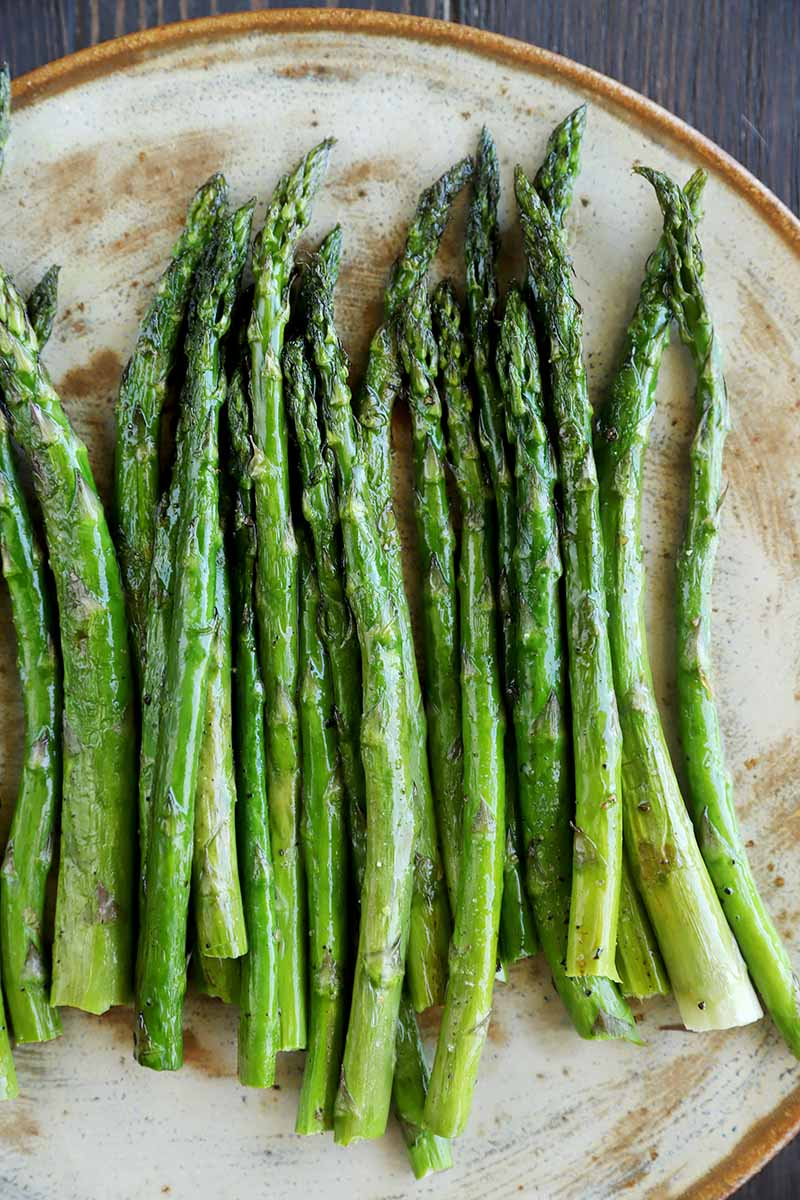 Vertical image of a plateful of cooked and seasoned asparagus.