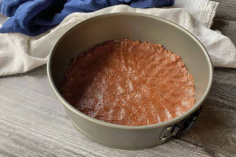 Horizontal image of a pressed chocolate crust on the bottom of a springform pan in front of blue and white towels.