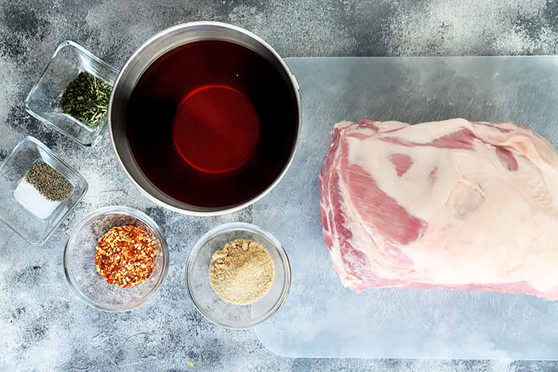 Horizontal image of a large piece of raw meat, a large bowl of vinegar, and small bowls of seasonings.