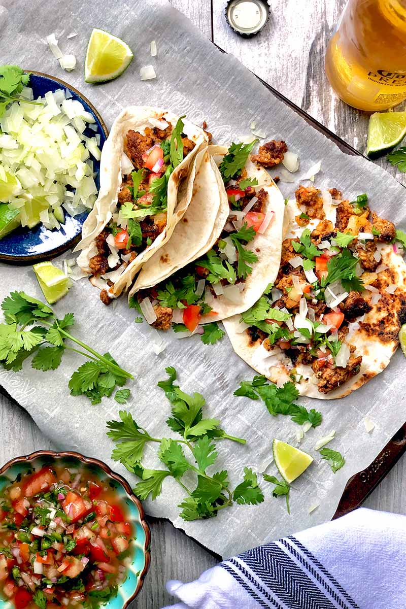 Vertical image of a row of tacos on a sheet pan lined with parchment paper with bowls of raw diced onion and pico de gallo.