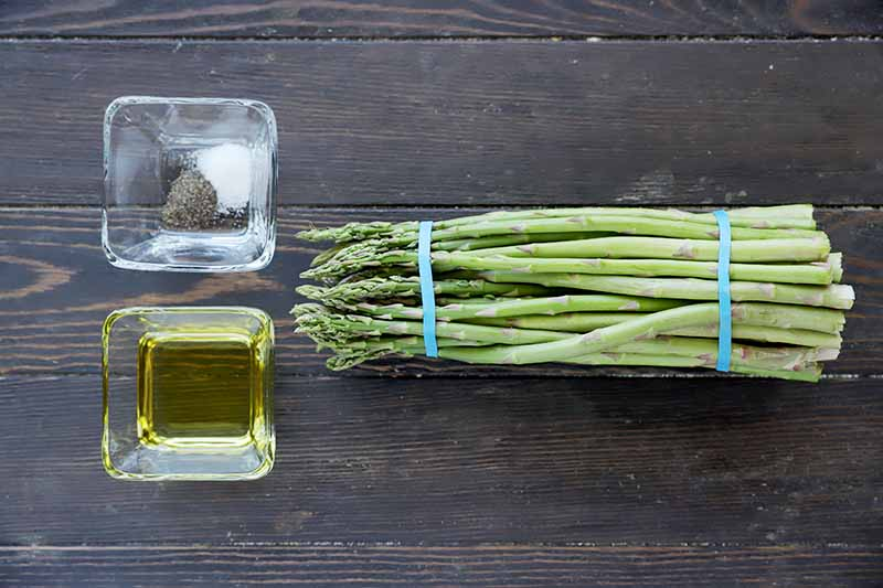 Horizontal image of a bunch of asparagus held by rubber bands next to a dish of oil and a dish of seasonings.