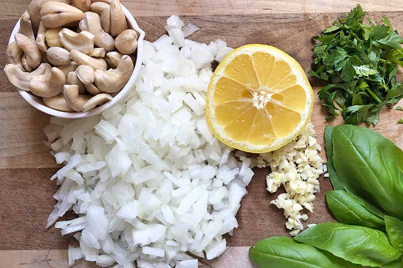 Horizontal image of chopped onions, a bowl of cashews, a wedge of lemon, mined garlic, and herbs.