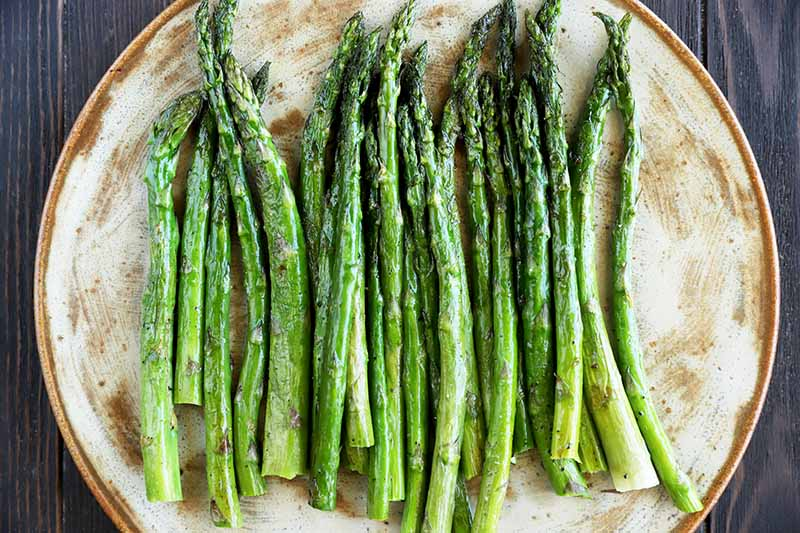 Horizontal image of a plateful of cooked and seasoned asparagus.