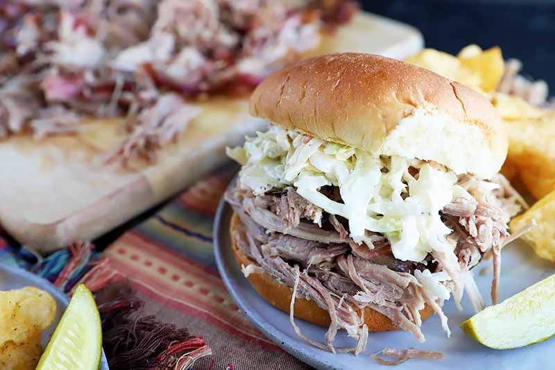 Horizontal image of a sandwich filled with shredded meat and coleslaw on a plate with pickles on top of a towel.