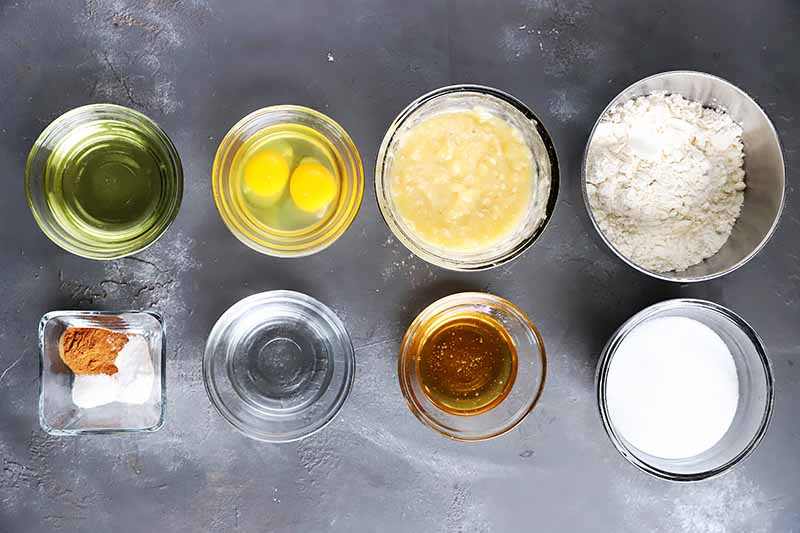 Horizontal image of assorted wet and dry ingredients in clear small glass bowls.