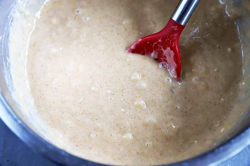 Horizontal image of stirring a very wet spiced batter with a red spoon.