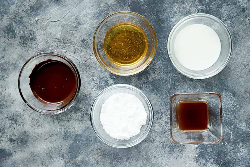 Horizontal image of ingredients to make a chocolate glaze in small glass bowls.