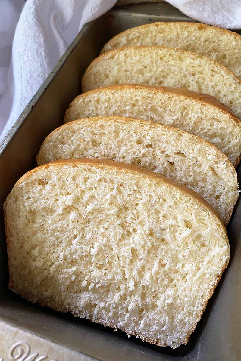 Vertical image of bread slices shingled in a pan.