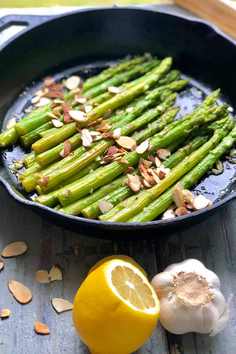 Vertical image of green cooked stalks in a cast iron pan topped with sliced almonds next to lemon and garlic.