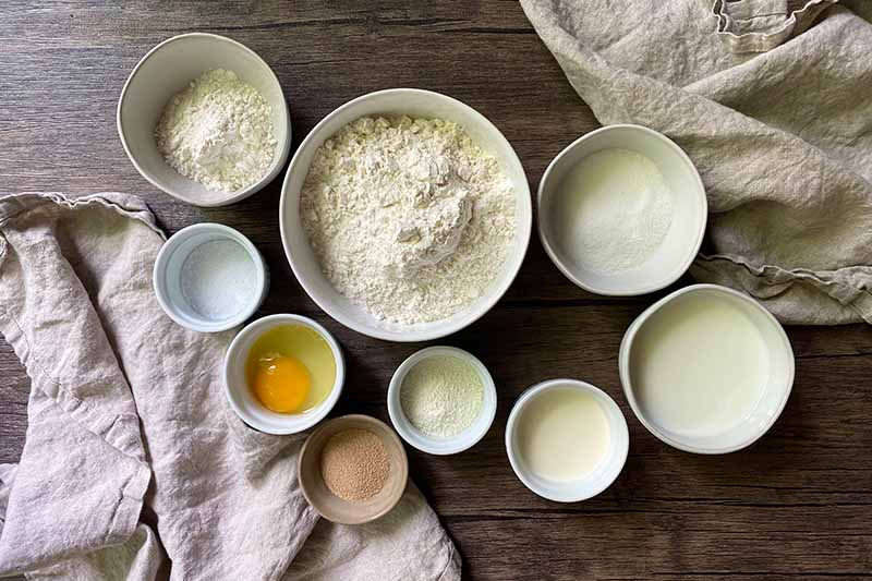 Horizontal image of small white bowls of assorted wet and dry ingredients.