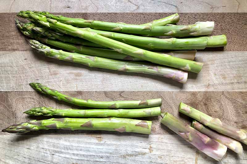 Horizontal image of prepping raw asparagus on a wooden cutting board.