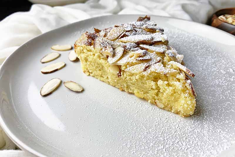 Horizontal image of a slice of yellow dessert garnished with sliced nuts and powdered sugar on a white plate.