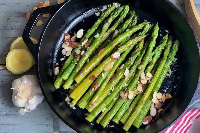 Horizontal top-down image of green vegetable stalks topped with sliced nuts in a cast iron pan next to lemon and garlic.