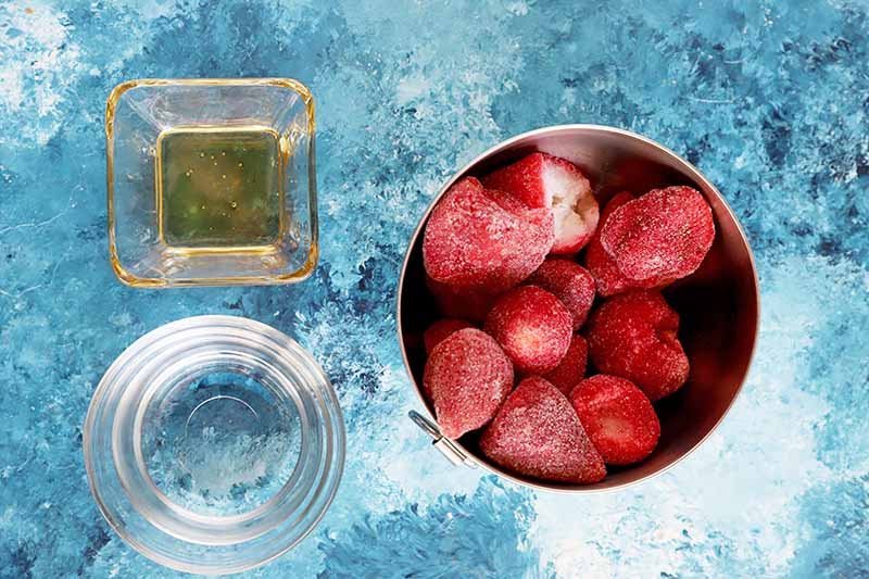 Horizontal image of a bowl of frozen strawberries, water, and honey.