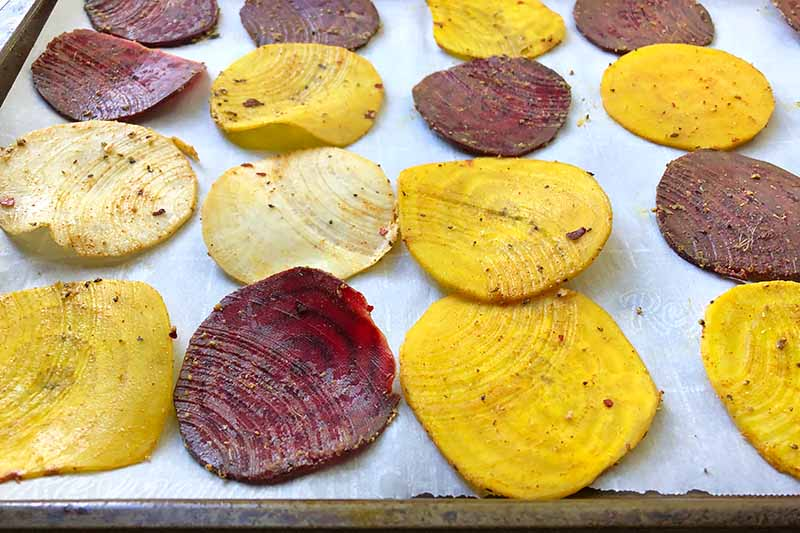 Horizontal image of thinly sliced beets and parsnips seasoned with spices on a baking sheet lined with parchment paper.