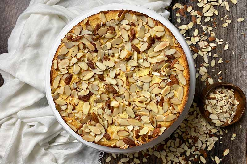 Horizontal image of a circular baked dessert topped with nuts next to a white towel.