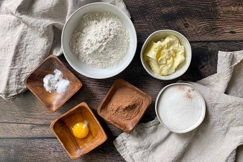 Horizontal image of assorted dry and wet ingredients in brown and white bowls.
