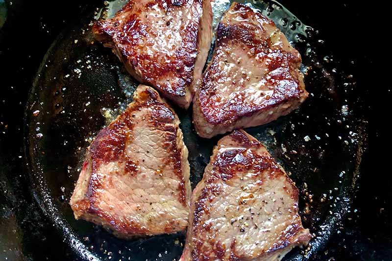 Horizontal image of four portions of seared steak in a skillet.