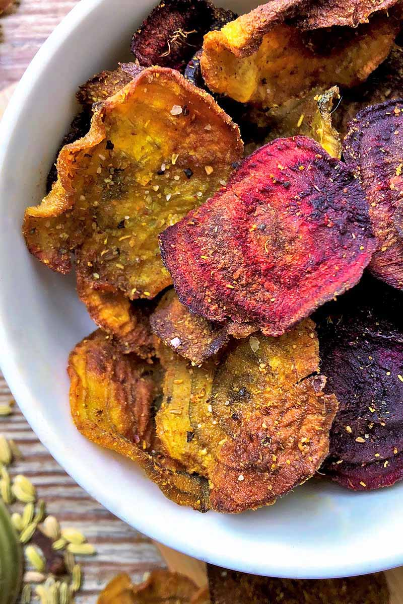 Vertical close-up image of thinly sliced and baked seasoned beets and parsnips in a white bowl.