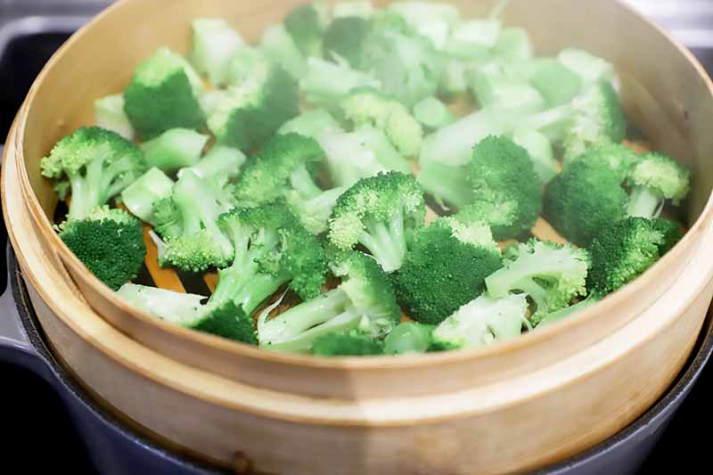Horizontal image of cooked broccoli in a steamer basket over a pot of steaming water.