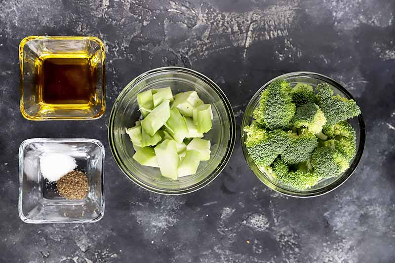 Horizontal image of the stalks and florets of a vegetable in bowls next to bowls of oil and seasonings.