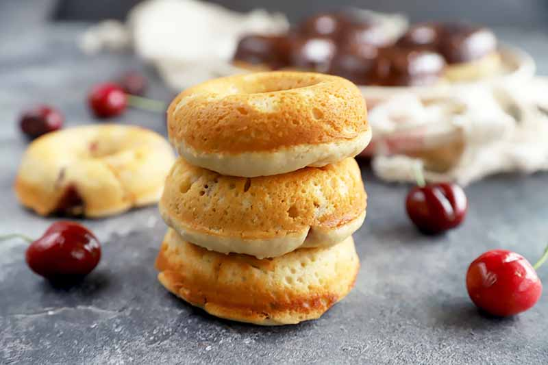 Horizontal image of a stack of plain doughnuts on a surface next to towels and cherries.