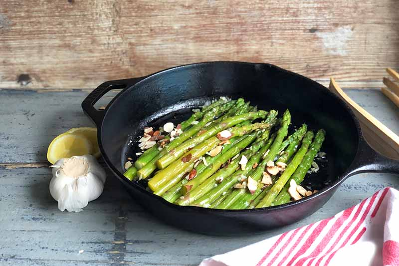 Horizontal image of green vegetables in a cast iron pan garnished with nuts next to a lemon and garlic.