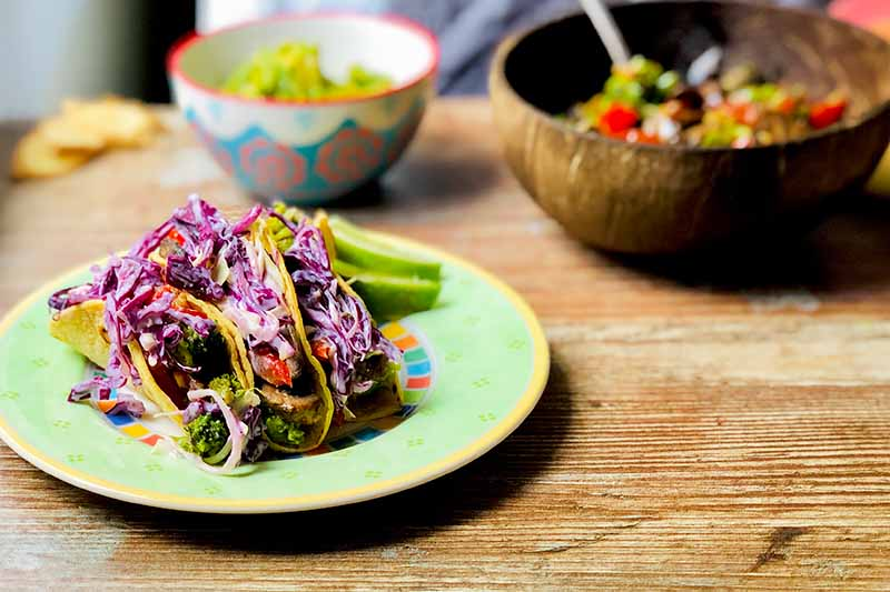Horizontal image of a green plate with three corn tortillas filled with slaw and other assorted vegetables next to two bowls.