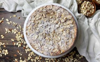 Horizontal image of a whole dessert topped with sliced nuts and powdered sugar over a white towel and more nuts.
