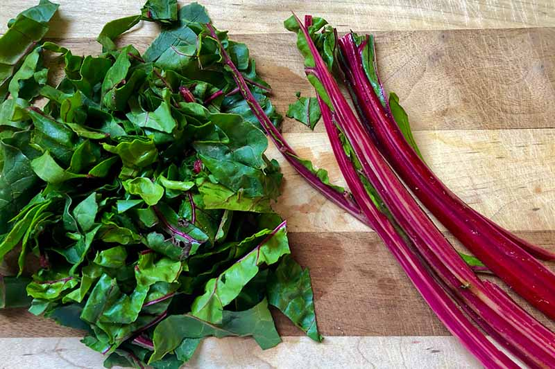 Horizontal image of the chopped leaves and whole stems of Swiss chard on a wooden cutting board.