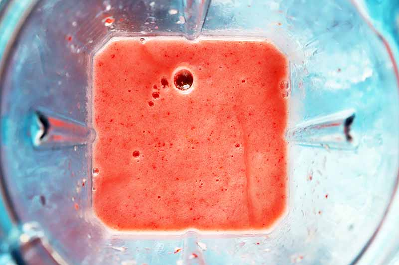Horizontal image of pureed strawberries in a blender.