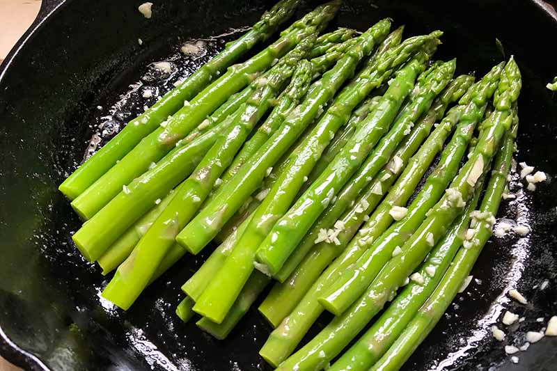 Horizontal image of cooking asparagus in butter and minced garlic in a cast iron skillet.