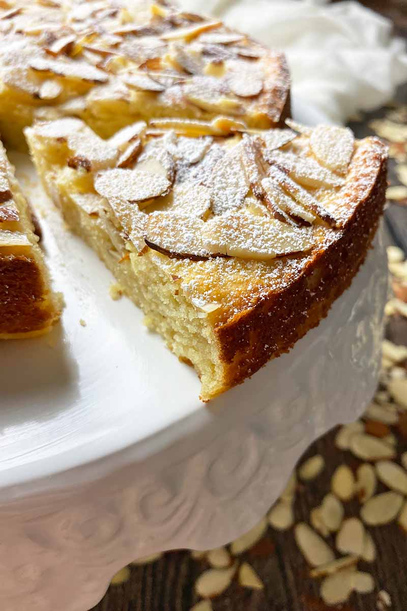 Vertical close-up image of a slice of yellow dessert garnished with sliced nuts and a fine dusting of powdered sugar on a white tray.