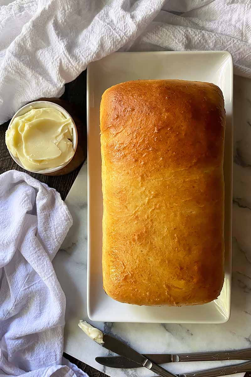 Vertical image of the top of a baked loaf on a white plate next to a bowl of butter surrounded by white towels.