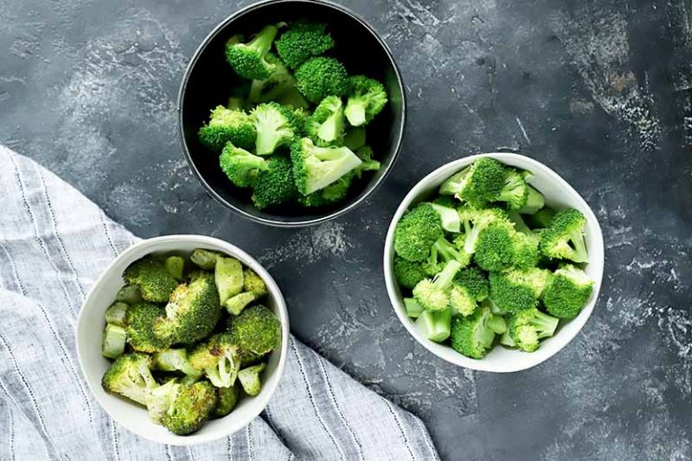 Horizontal image of three small bowls with cooked green vegetables.