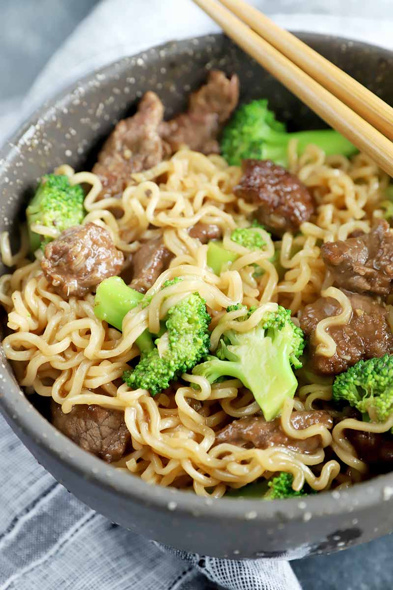 Vertical image of a bowl of noodles, green vegetables, and sliced beef next to chopsticks.