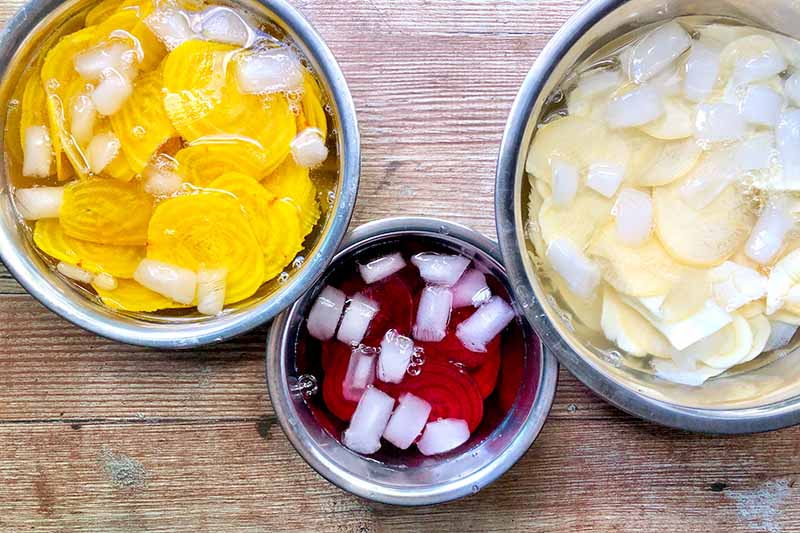 Horizontal image of soaking slices of beets and parsnips in ice water in three separate bowls.